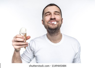 Cheerful and joyful man is eating an ice cream not very accurate but with big pleasure. Isolated on white background.