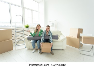 Cheerful joyful young couple charming girl and handsome man holding a box with things and a pot with a plant while moving to a new apartment. Housewarming and mortgage concept.