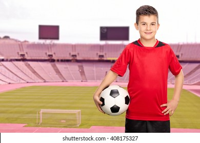 Cheerful junior football player in a red jersey posing in a football stadium and holding a ball