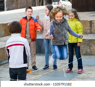 Cheerful junior school kids playing in jump rope game at city street