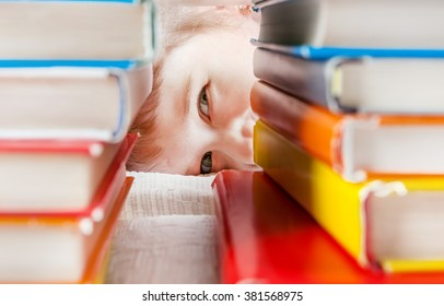 Cheerful Kid Behind the Books on the Sofa