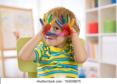 cheerful kid boy showing his hands painted in bright colors.