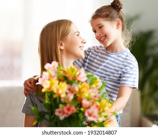 Fröhliches Kind, das am Müttertag auf einem Sofa mit Blumenstrauß der Alstroemeria sitzt
