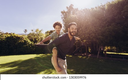 Cheerful kid enjoying a ride on the back of his father with arms open. Father walking in park carrying his son on his back on a sunny day.