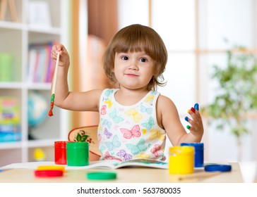 cheerful kid girl with fingers painted in bright colors