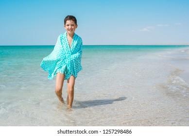 A cheerful kid on the beach on a sunny summer day wrapped in a bright beach towel.