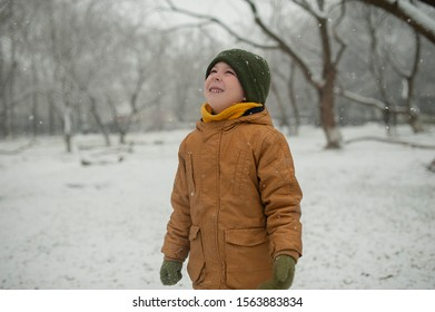 cheerful kid in a yellow down jacket and military hat rejoices at snow in winter catches snowflakes on his face