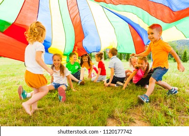Cheerful kids hiding under rainbow canopy