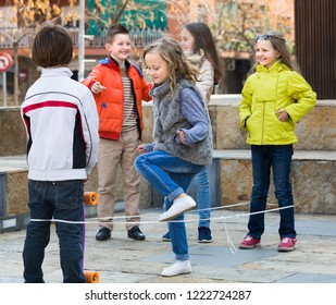 Cheerful kids playing in jump rope game at city street