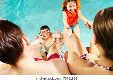 Cheerful kids playing with parents in swimming pool