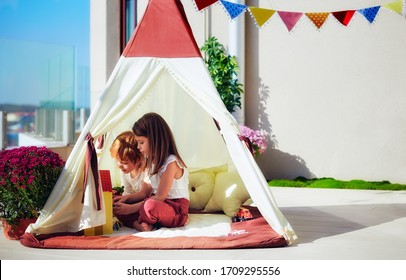 cheerful kids are playing in teepee tent on a sunny patio