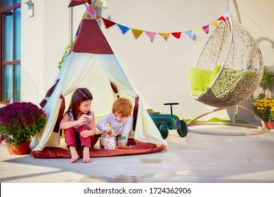 cheerful kids are playing in teepee tent, eating sweets on a sunny patio