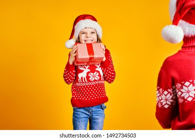 Cheerful kids in Santa hats and red sweaters standing with presents in gift boxes on yellow background