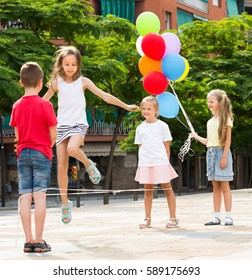 Cheerful kids in school age playing together with chinese jumping rope outdoors