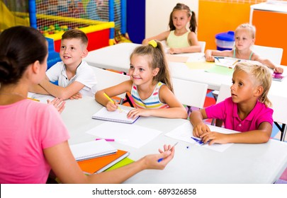 Cheerful kids sitting and listening teacher in elementary school class