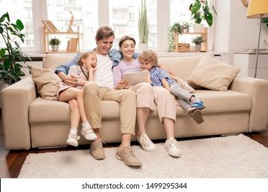 Niños alegres y sus padres en ropa informal relajándose en el sofá en el salón y viendo dibujos animados en tableta