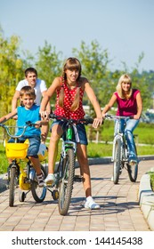 Cheerful kids and their parents riding bikes