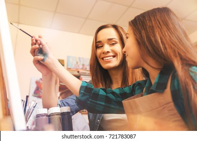 Cheerful lady helping teenage girl with painting
