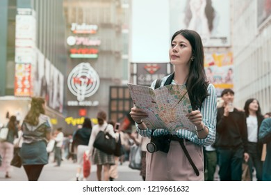 Cheerful lady searching direction on location map while traveling abroad in japan. young traveler standing in the shopping center. Asia travel vacation in Japan.