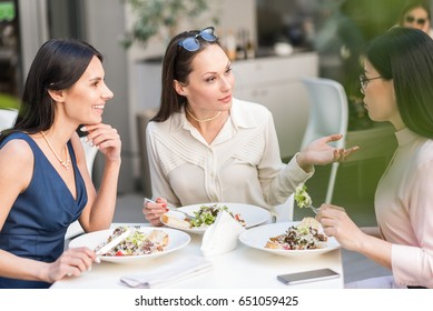 Cheerful lady speaking with colleagues in cafe