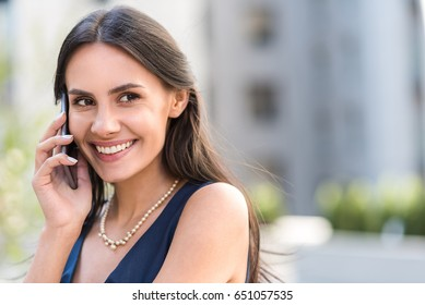 Cheerful lady telling by mobile