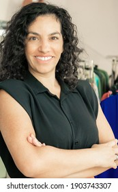 Cheerful Latin black haired woman standing with arms folded near rack with dresses in clothes shop, looking at camera and smiling. Boutique customer or shop assistant concept