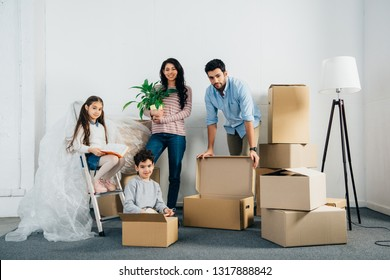 cheerful latin family standing near boxes while moving into new home
