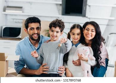 cheerful latin kid holding keys from new home near happy hicpanic family