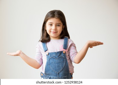 Cheerful Latin kid with shrug gesture asking something and looking at camera. Portrait of little girl in denim overalls. Isolated on white. Question concept