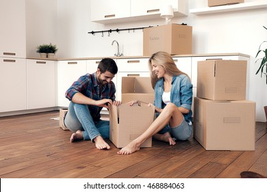 Cheerful and laughing couple unpacking boxes in kitchen on floor