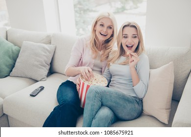 Cheerful laughing excited positive mother and daughter eating pop-corn looking tv, television sitting in living room indoor watching funny comedy, comfort domestic lifestyle free time