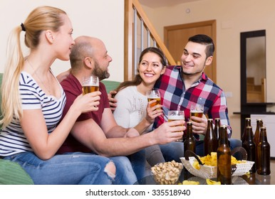 Cheerful laughing young adults drinking beer at home. Selective focus