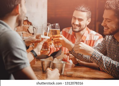 Cheerful laughing young boys drink beer, clinking glasses in bar. On table snacks cans.