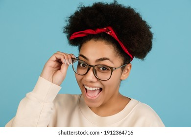 Cheerful laughs. African-american beautiful woman's portrait isolated on blue studio background with copyspace. Female model with eyewear. Concept of human emotions, facial expression, sales, ad