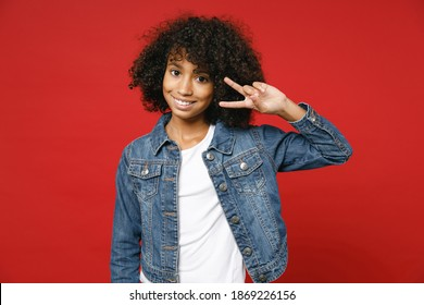 Cheerful little african american kid girl 12-13 years old in casual denim jacket showing victory sign isolated on bright red color background children studio portrait. Childhood lifestyle concept