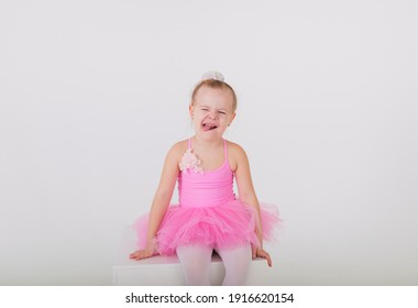 cheerful little ballerina in a pink dress with a tutu skirt sits on a white background with space for text