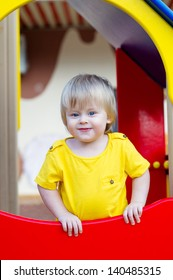 Cheerful little boy in bright yeallow t-shirt on the playground