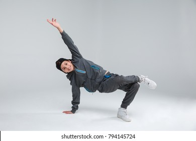 A cheerful little boy dressed in a gray tracksuit, actively dancing standing on one arm and one leg. Gray background.