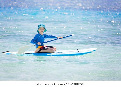 cheerful little boy enjoying stand up paddleboarding alone, active vacation concept