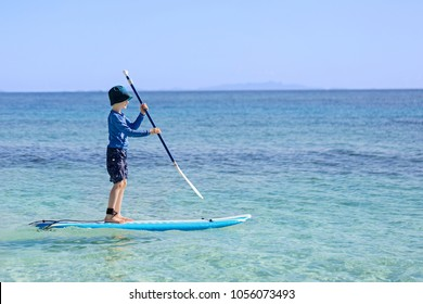 cheerful little boy enjoying stand up paddleboarding alone, active vacation concept, copy space on right