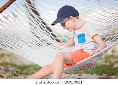 cheerful little boy enjoying tropical vacation in hammock