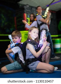 Cheerful little boy and girl sitting back to back with laser pistols in dark lasertag room during game with parents