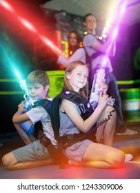 Cheerful little boy and girl sitting back to back on bright beams with laser pistols in dark lasertag room during game with parents