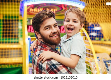 Cheerful little boy having fun with his dad at the entertainment centre