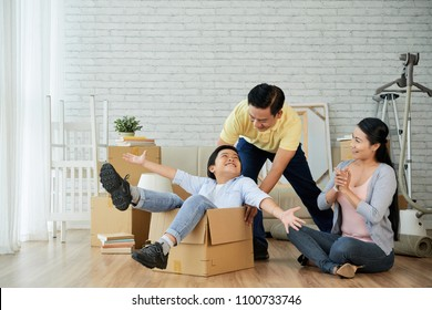 Cheerful little boy having fun with middle-aged parents while riding in cardboard box at new apartment, interior of spacious living room on background