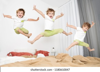 Cheerful little boy  jumping on bed at home. lot of children.