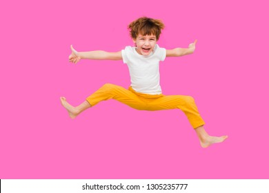 Cheerful little boy  jumping on a pink background
