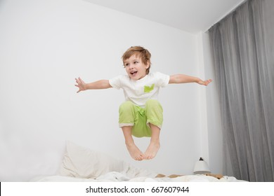 Cheerful little boy  jumping on bed at home