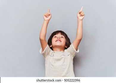Cheerful little boy looking and pointing up with both hands over gray background