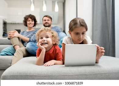 Cheerful little boy lying on cozy sofa and watch educational program with his parents while his elder sister wrapped up in playing computer game, interior of studio apartment on background